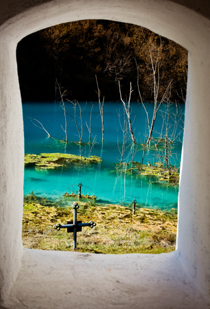 Chiesa con il suo cimitero sotto l'acqua contaminata a Geamana, in Romania. Lago inquinato con residui minerari che distrussero un villaggio. Archivio Fotografico - 89323364