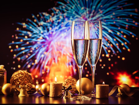 two champagne glasses against holiday lights and fireworks new year celebration stock photo