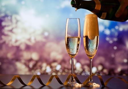 Champagne in glazen gieten tegen vakantielichten Stockfoto - 89409916