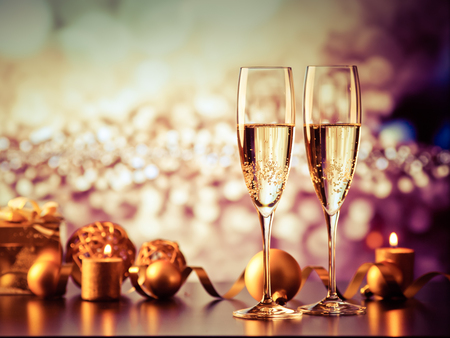 休日ライトと新年のお祝いの花火に対する 2 つのシャンパン グラス