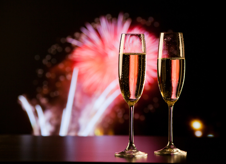 two champagne glasses against holiday lights and fireworks - new year celebration Reklamní fotografie