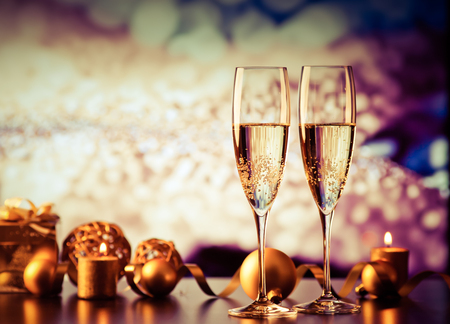 uncork: two champagne glasses against holiday lights and fireworks - new year celebration Stock Photo