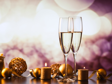 two champagne glasses against holiday lights and fireworks - new year celebration Stockfoto