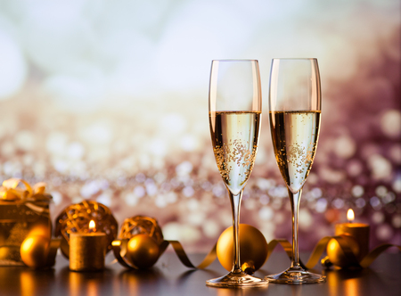 two champagne glasses against holiday lights and fireworks - new year celebration Stock Photo