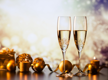 two champagne glasses against holiday lights and fireworks - new year celebration Archivio Fotografico