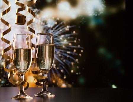 twee champagneglazen met linten tegen vakantielichten en vuurwerk - Nieuwjaarsvieringen Stockfoto