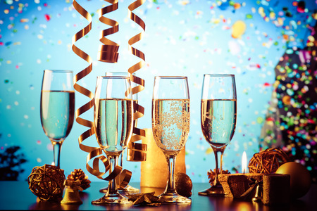 champagne glasses against holiday lights ready for New Years eve party Stock Photo