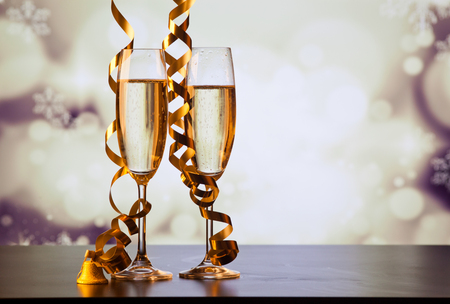 fizz: two champagne glasses with ribbons against holiday lights and fireworks - New Year celebrations