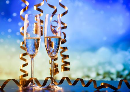 Dos copas de champán con cintas contra luces navideñas y fuegos artificiales - celebraciones de año nuevo Foto de archivo - 89396040