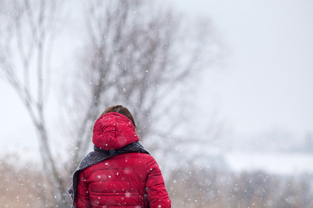 woman in red coat walking in heavy snowfall in the countryside Banque d'images