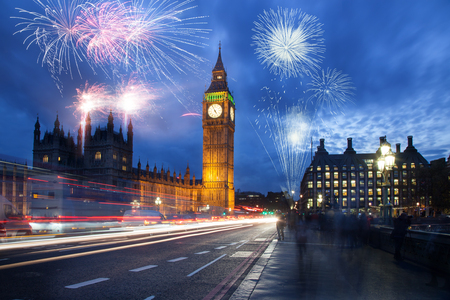 explosive fireworks display fills the sky around Big Ben. New Year's Eve celebration in the city Imagens - 90961630