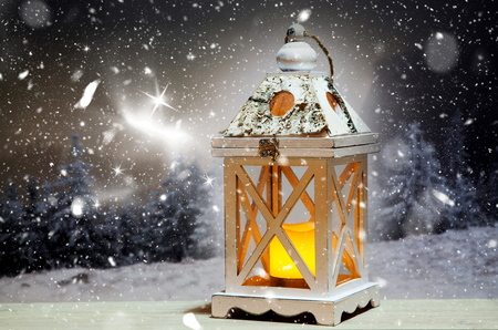 christmas lantern and snowy firs in the background