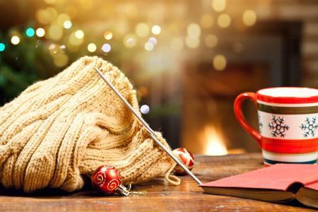 warm woolen knitwear and burning fireplace - cozy winter at home Stock Photo