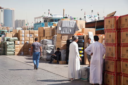 DUBAI, UAE- May 3, 2013: People going on with their daily lives in the old town of Dubai loading cargo ships in the port. Editorial