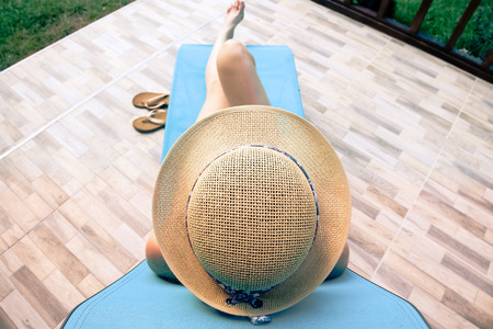 top view of woman relaxing on sunbed on a hot summer day - focus on straw hat