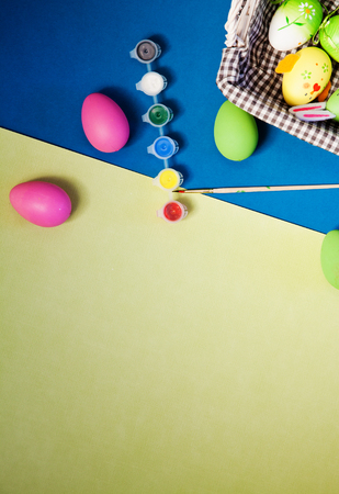 colorful painted pink, blue, green easter eggs on modern blue and yellow background Stock Photo