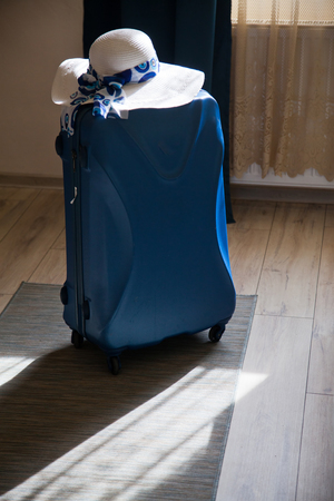 packed blue suitcase in room and straw hat ready for the summer holiday