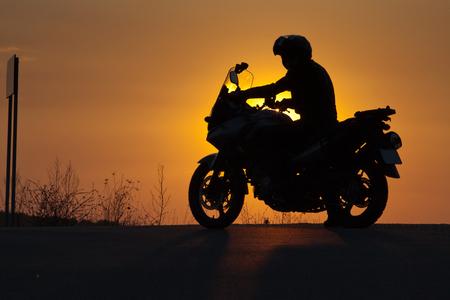 silueta de ciclista en una moto admirando la puesta de sol - espacio para el texto