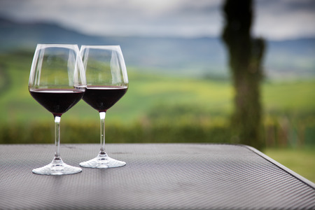 two glasses of red wine against beautiful landscape in Tuscany Stock Photo