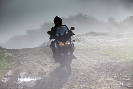 silhouette of a man riding a motorbike on foggy road in early morning 版權商用圖片