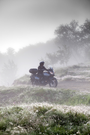man riding a motorbike on foggy road in early morning