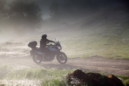 silhouette of a man riding a motorbike on foggy road in early morning