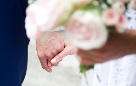 bride and groom holding hands and wedding bouquet of beautiful pink roses Stock Photo