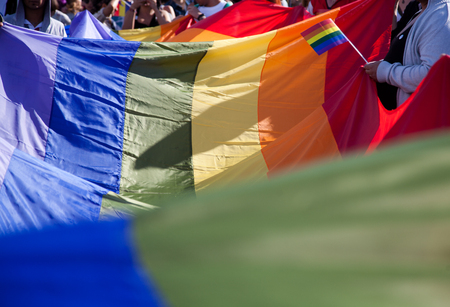 people holding giant rainbow flag at pride parade - LGBT symbol