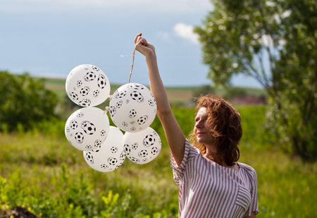 woman holding balloon with footballs - soccer supporter - world cup