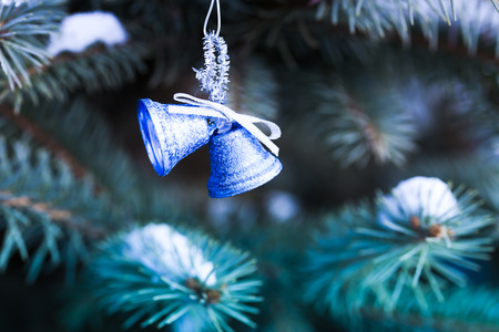 blue bells christmas decoration hanging on snowy tree