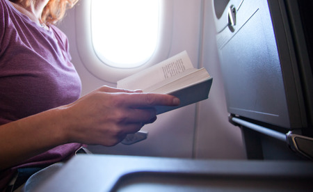 woman reading a book on airplane