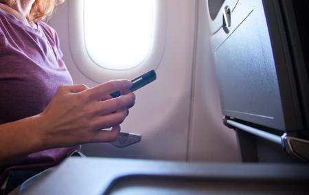 woman using smartphone on airplane