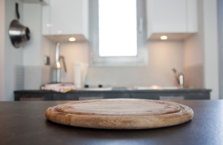 blurred kitchen interior with wooden cutting board and desk space