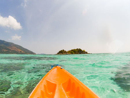 kayaking in crystal clear tropical waters - kayak heading to isolated beach in Ko Tarutao national park Stock Photo