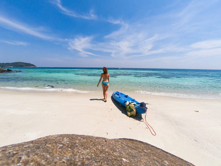 woman with a kayak on an isolated beach in Andaman sea, Koh Lipe - solo travel