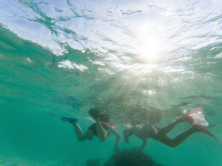 couple snorkeling in crystal clear tropical waters