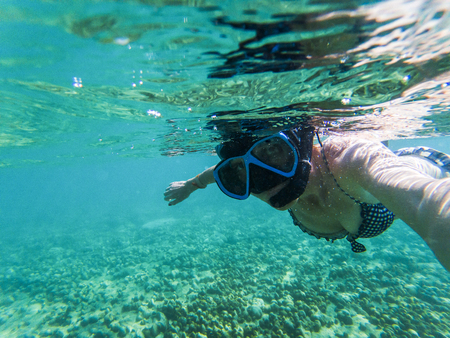 Frau, die ein Unterwasser-Selfie beim Schnorcheln im kristallklaren tropischen Wasser macht