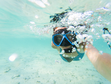 woman taking an underwater selfie while snorkeling in crystal clear tropical water