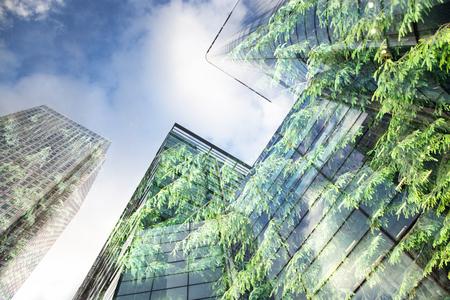 zielone miasto - podwójna ekspozycja soczystej zieleni lasu i okien nowoczesnych wieżowców