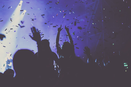 cheering crowd with raised hands and falling confetti at concert - music festival Stock Photo