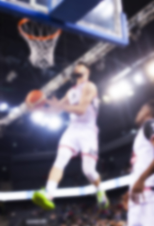 blurred image of basketball player during slam dunk - game background