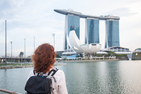 woman tourist with a backpack looking at Marina Bay Sands in Singapore Editorial