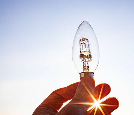 hand holding light bulb against sunny sky Reklamní fotografie