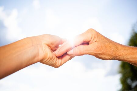 close-up of tender gesture between two generations. Young woman holding hands with a senior lady. Blue sky background Reklamní fotografie