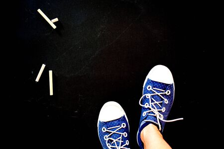 top view of feet wearing blue dotted sneakers on black background with copy space