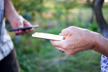 hands of elderly couple using smartphone for data transfer