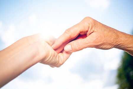 close-up of tender gesture between two generations. Young woman holding hands with a senior lady. Blue sky background Фото со стока