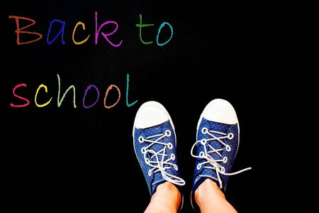 chalk and kids feet on black background wearing sneakers - back to school concept
