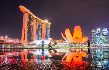 SINGAPORE, SINGAPORE - MARCH 2019: Skyline of Singapore Marina Bay at night with Marina Bay sands and Art Science museum reflecting in a pond after rain. Vibrant night scene