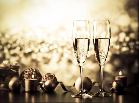 Dos copas de champán contra luces navideñas y fuegos artificiales - celebración de año nuevo Foto de archivo